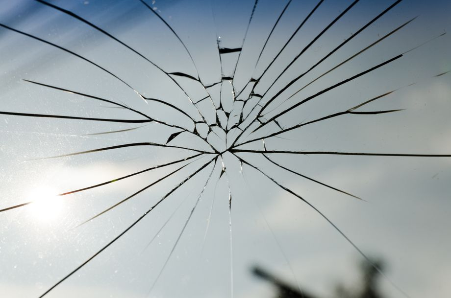 Broken, fractured, splintered glass with large cracks in the very centre of the image.
